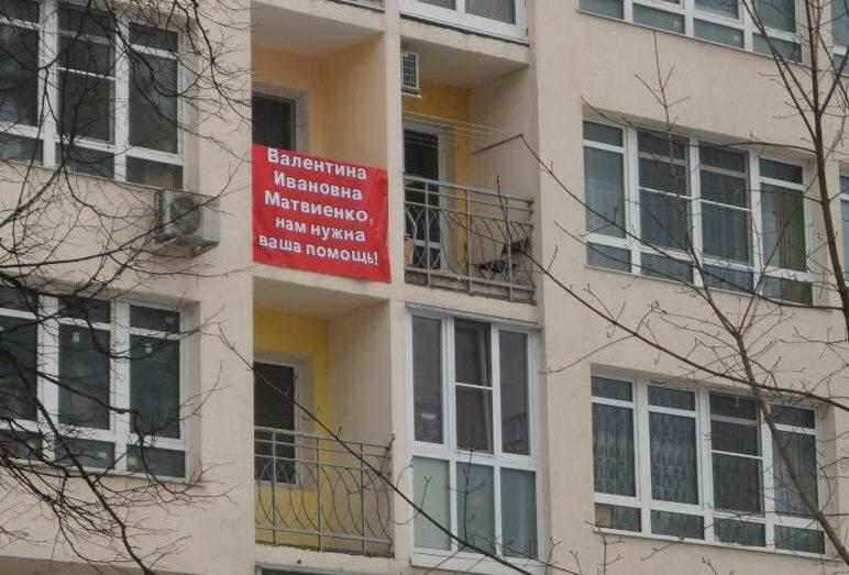 Жители дома вывесили плакаты с просьбой о помощи.