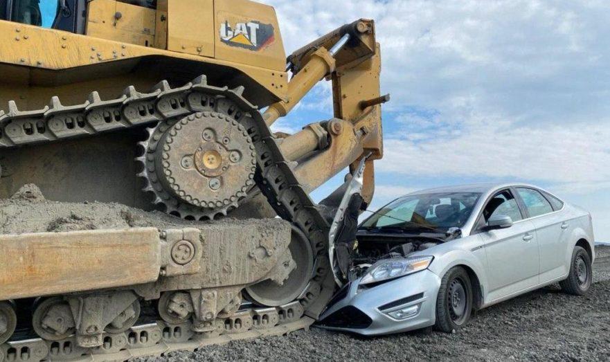 Трактор давит машину